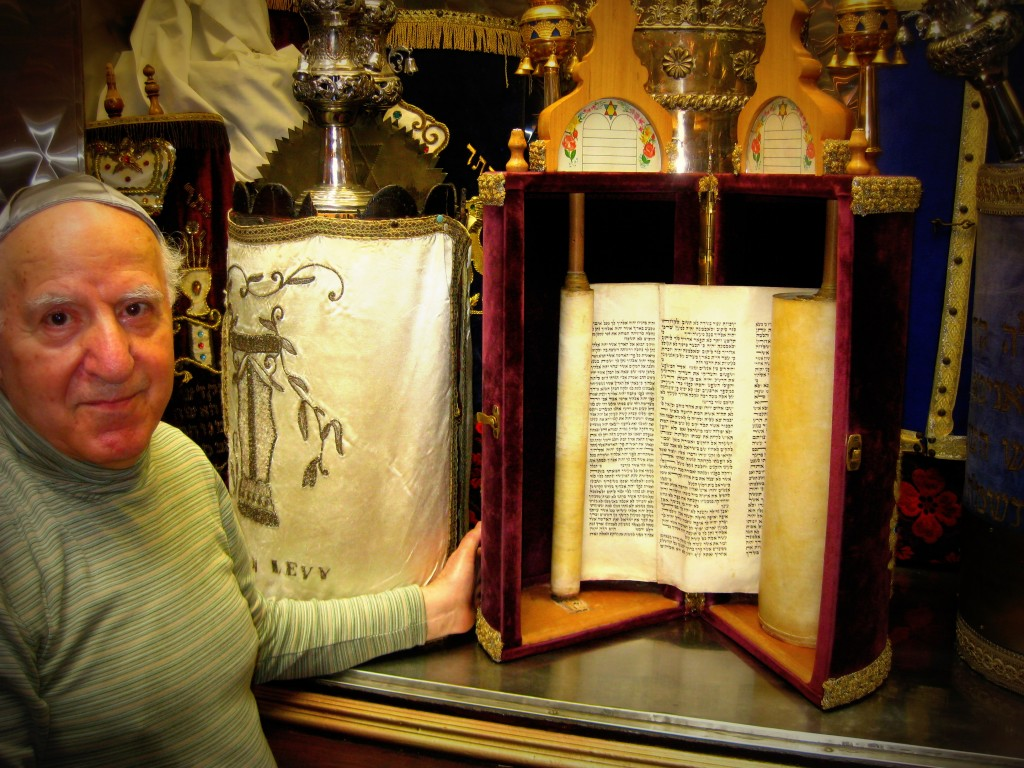 Lower East Side native Sol Matsil displays torah scrolls in Kehila Kedosha Janina-the Western Hemisphere's sole Greek Orthodox Jewish synagogue.